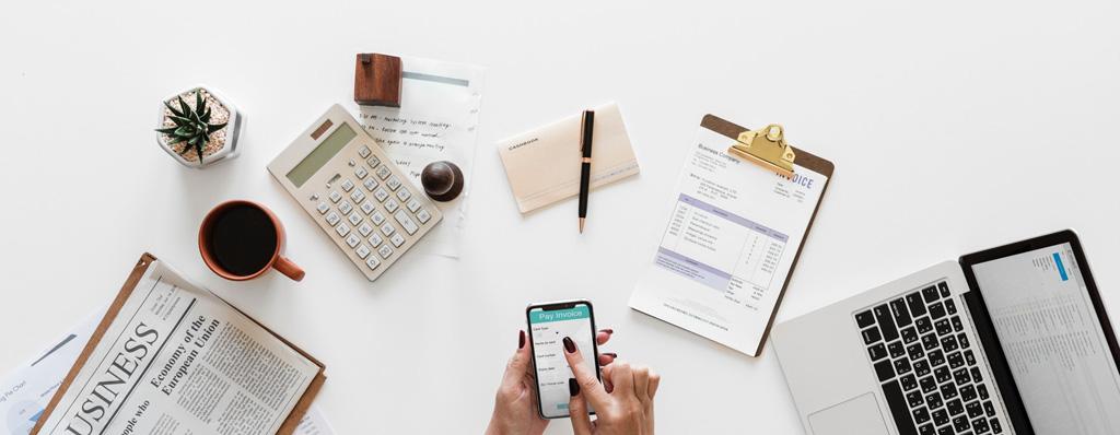 Schreibtisch mit Zeitung, Rechner, Stiften, Laptop und mehr als Seitenbild
